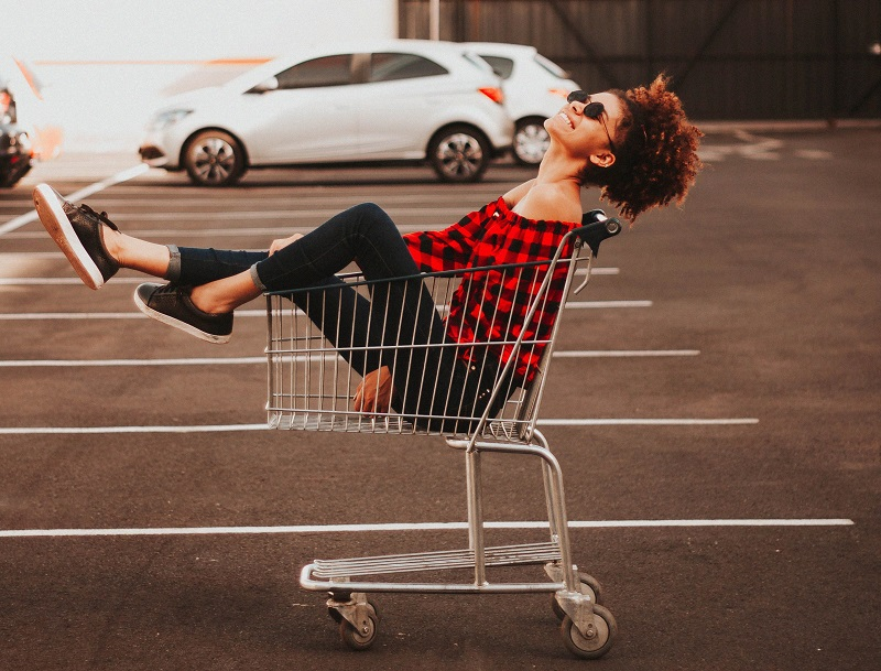 Girl inside supermarket storage cart, millenials are making more money, and spending it